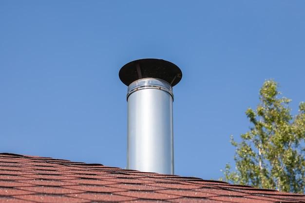 Tubo de chimenea de metal de acero inoxidable en el techo de la casa