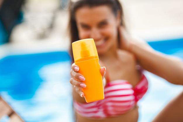 Un tubo de crema de protección solar en la parte delantera. chica con crema de protección solar.