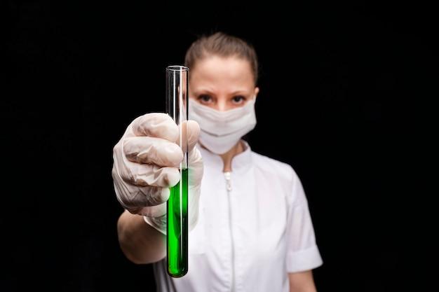 Un tubo de ensayo con un líquido o sustancia luminosa de color verde brillante en la mano extendida de una joven trabajadora médica o científica con una máscara
