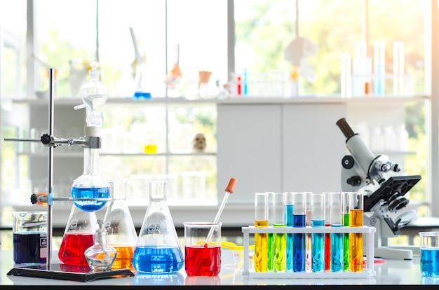 Tubo de ensayo de líquidos químicos y microscopio en laboratorio.