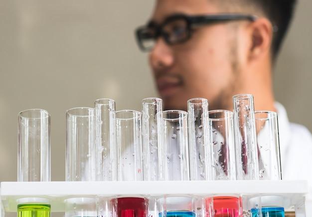 Tubo de ensayo muchos colores en el laboratorio con científicos en tierra