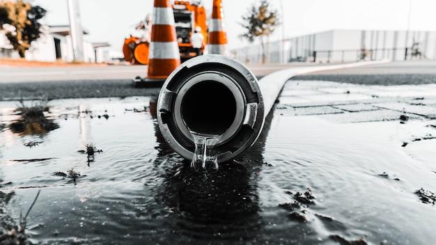 Tubo gris con agua saliendo de su agujero