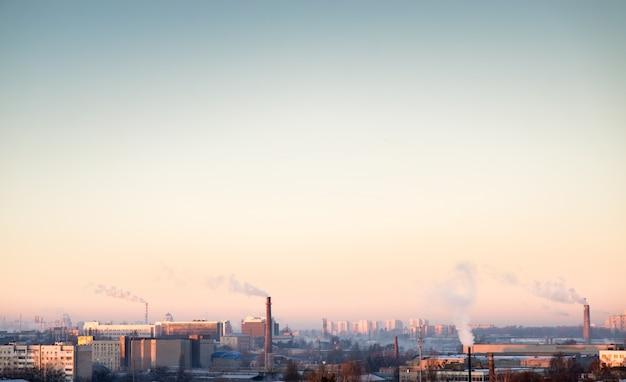 Tubo con humo naranja en la puesta de sol de invierno