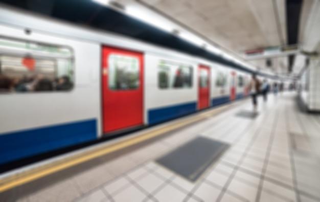 Tubo de londres - tren subterráneo en la plataforma, imagen de fondo borrosa.