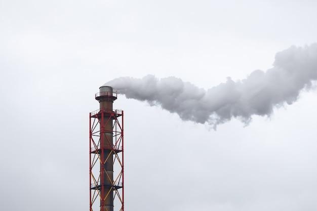 Tubo de metal del que sale humo blanco en el cielo nublado