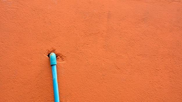 Tubo plástico azul en la pared anaranjada del cemento.