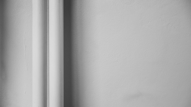Tubo plástico blanco en la pared del cemento blanco con la sombra.