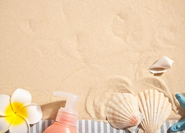 Tubo de protector solar, estrellas de mar, plumeria frangipani y conchas marinas en la arena