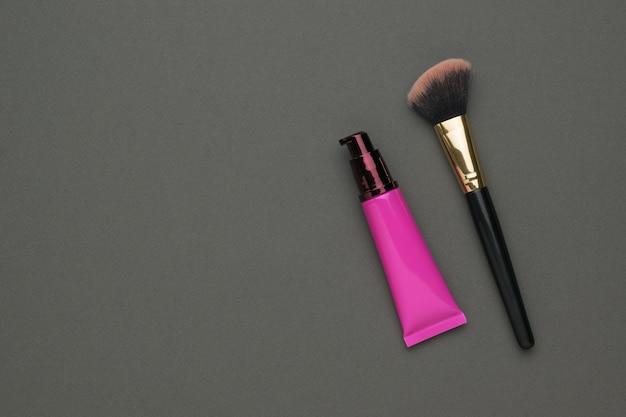 Un tubo rojo de crema cosmética y una brocha de maquillaje sobre un fondo gris oscuro. kit de cuidado facial.