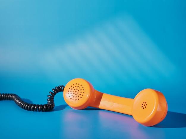 Tubo de teléfono naranja vintage sobre fondo azul.