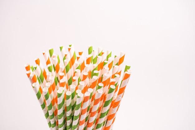 Tubos para beber a rayas verdes, rojas y blancas en un vaso aislado en una pared blanca