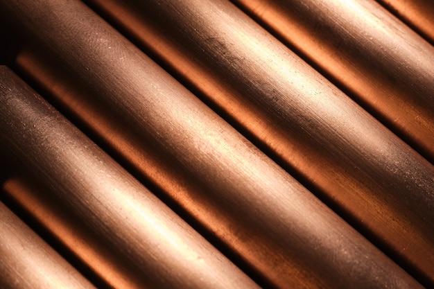 Tubos de cobre que reflejan la luz, fondo metálico, líneas diagonales.