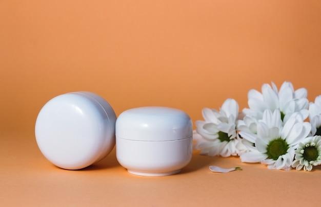 Tubos cosméticos blancos con crema facial, loción corporal o limpiador sobre un fondo beige con flores blancas, cuidado de la piel facial o corporal, tratamiento de belleza, cosméticos orgánicos