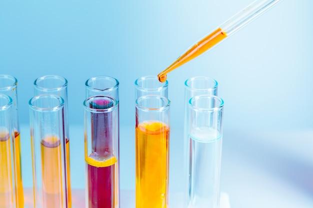 Tubos de ensayo de laboratorio con líquidos rojos y amarillos sobre azul claro