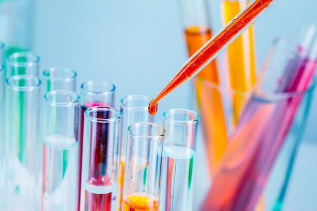 Tubos de ensayo de laboratorio con líquidos rojos y amarillos sobre fondo azul claro