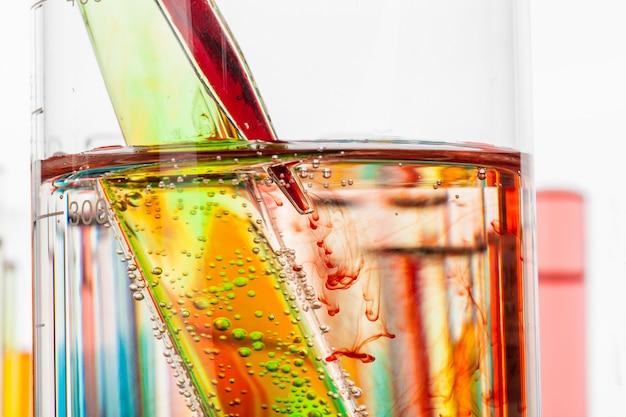Tubos de ensayo con productos químicos coloridos de cerca en laboratorio