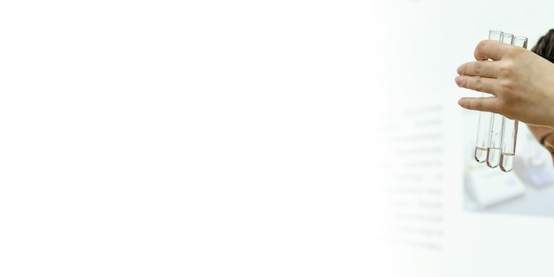 Tubos de ensayo de vidrio en sus manos y tubos de ensayo con muestras de sangre para exámenes médicos en un soporte de laboratorio blanco como la nieve. el experto forense sostiene un tubo de ensayo con una muestra de adn. una prueba de paternidad. bandera.
