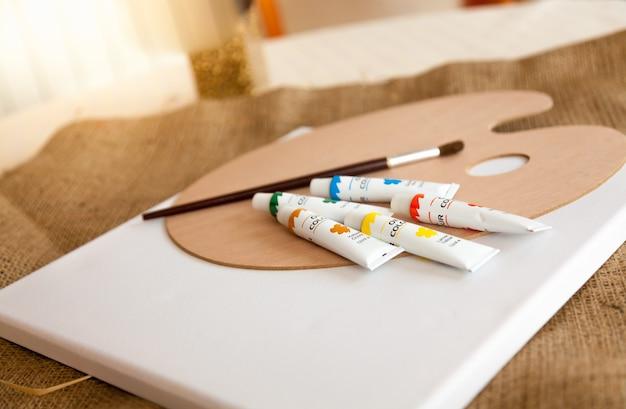 Tubos de pintura de aceite, paleta y cepillo sobre la mesa en la sala de estar