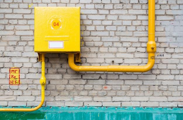 Tubos de suministro de gas con tablero contra pared de ladrillos.