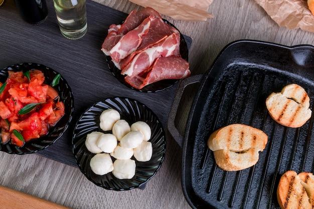 Tueste el pan en la sartén a la parrilla cerca de los platos con mozzarella, jamón y tomate. bruschettagredient. vista superior.