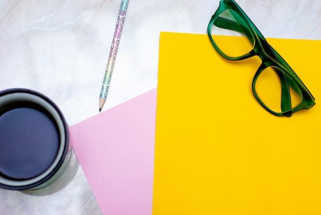Tulipán amarillo, café, vasos verdes y papel de colores sobre fondo de mármol