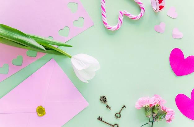 Tulipán blanco con corazones de papel en mesa