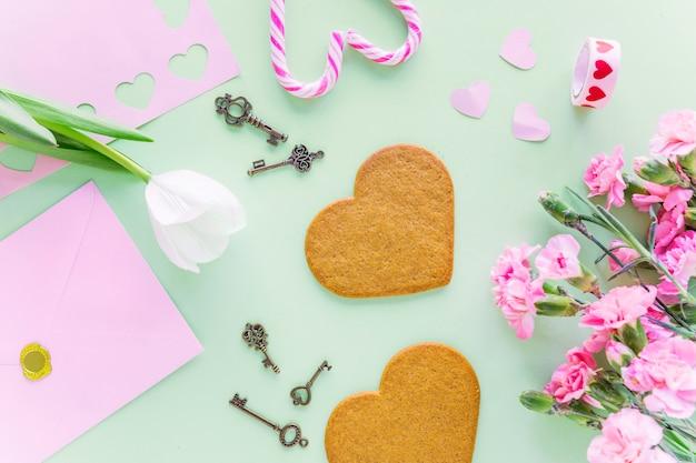 Tulipán blanco con galletas de corazón en la mesa