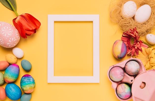 Tulipán; flor de gerbera; huevos de pascua y marco de borde blanco vacío sobre fondo amarillo