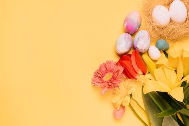 Tulipán; flores de gerbera y lily con huevos de pascua sobre fondo amarillo