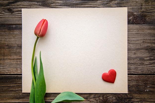 Un tulipán rojo y un pequeño corazón rojo en un trozo de papel