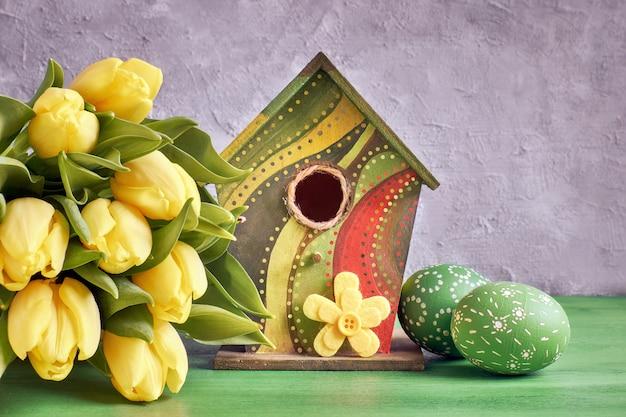 Tulipanes amarillos, casita para pájaros y huevos de pascua pintados con flor decorativa de fieltro