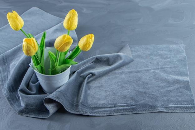 Tulipanes amarillos en un cubo sobre un trozo de tela, sobre el fondo blanco. foto de alta calidad