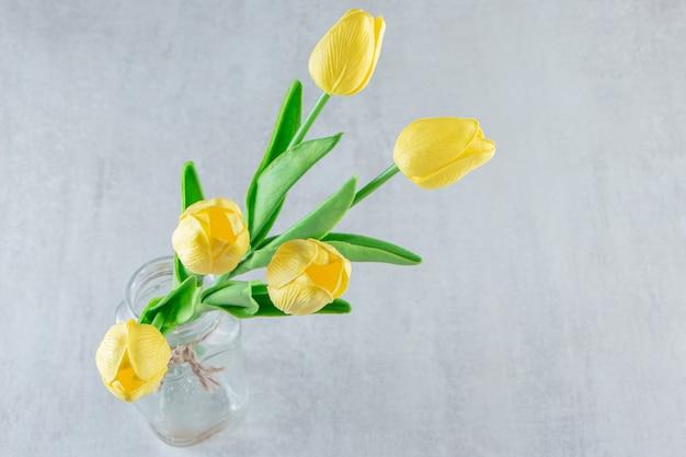 Tulipanes amarillos en un frasco, sobre la mesa blanca.