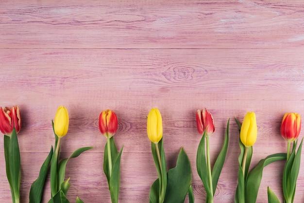 Los tulipanes amarillos, rojos y rosados en un fondo de madera rosado copian el espacio.