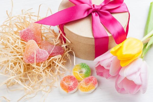 Tulipanes amarillos rosados y caja de regalo con cinta roja