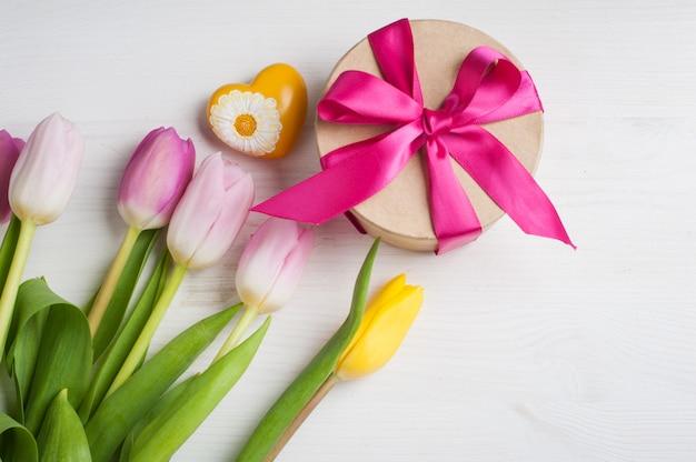 Tulipanes amarillos rosas rojos y caja de regalo con cinta roja