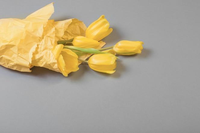 Tulipanes amarillos sobre fondo gris, color de 2021
