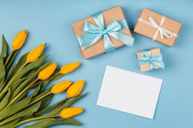 Tulipanes amarillos con tarjeta en blanco y regalos