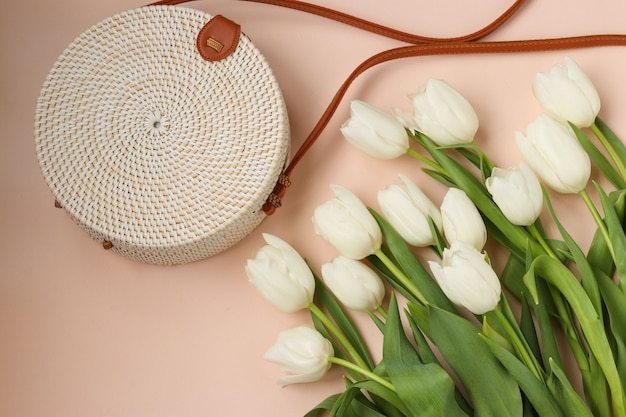 Tulipanes blancos y bolso redondo de mimbre para mujer sobre fondo rosa