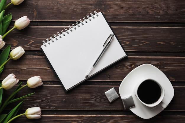 Tulipanes blancos en una mesa de madera con una taza de café y un cuaderno vacío