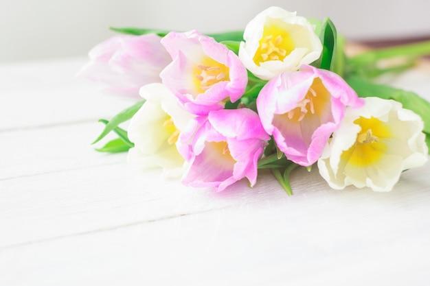 Tulipanes blancos y púrpuras sobre un fondo de madera blanco