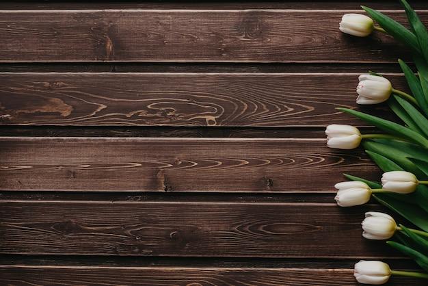 Tulipanes blancos sobre un fondo marrón de madera. tarjeta de felicitación en blanco para el día de san valentín
