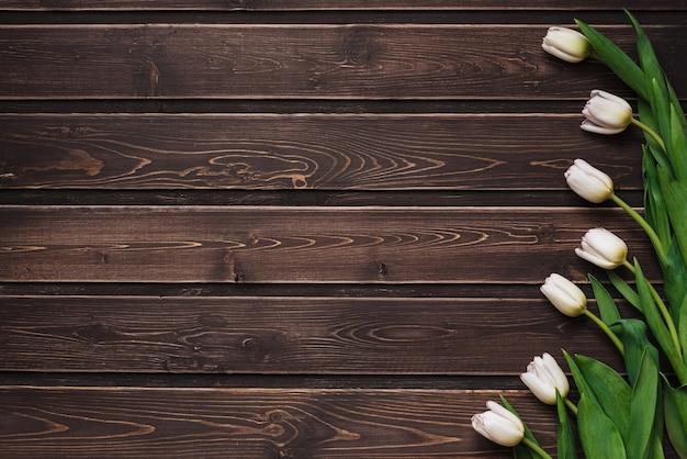 Tulipanes blancos sobre un fondo de mesa de madera marrón. tarjeta de felicitación en blanco para el día de san valentín