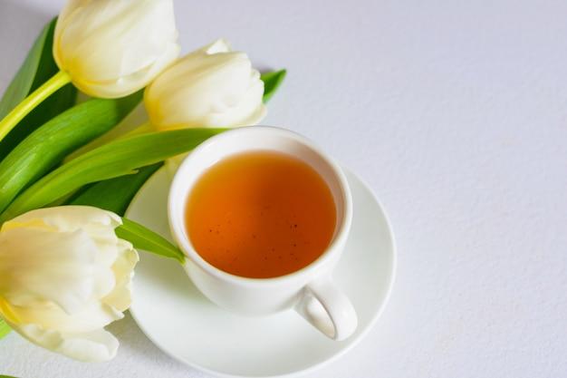 Tulipanes blancos tiernos de primavera y una taza de té sobre fondo blanco.