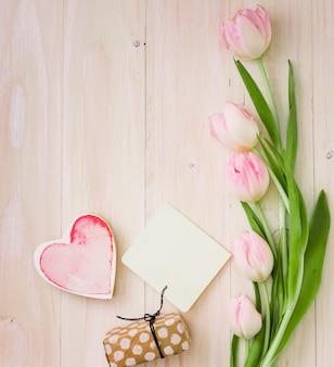 Tulipanes con caja regalo y papel sobre mesa.