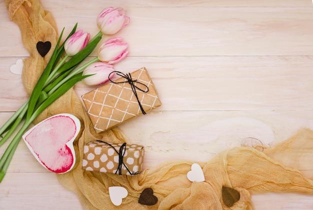 Tulipanes con cajas de regalo y corazones.