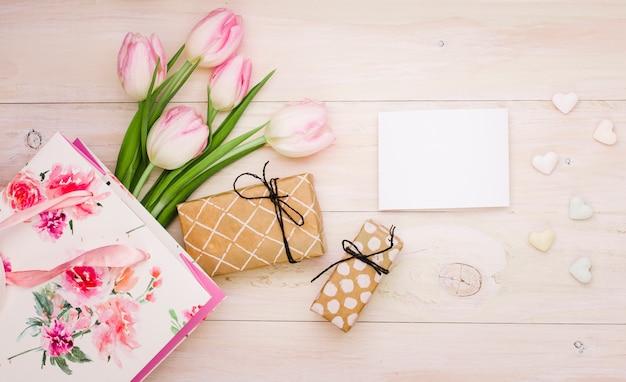 Tulipanes con cajas de regalo y papel en blanco.