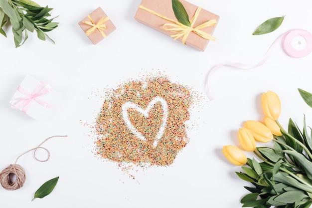 Tulipanes, cajas con regalos y cintas alrededor de los dulces en forma de corazón