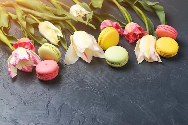 Tulipanes de colores y macarrones sobre fondo negro. espacio para texto.