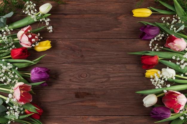Tulipanes coloridos y flor de aliento del bebé en mesa con textura de madera
